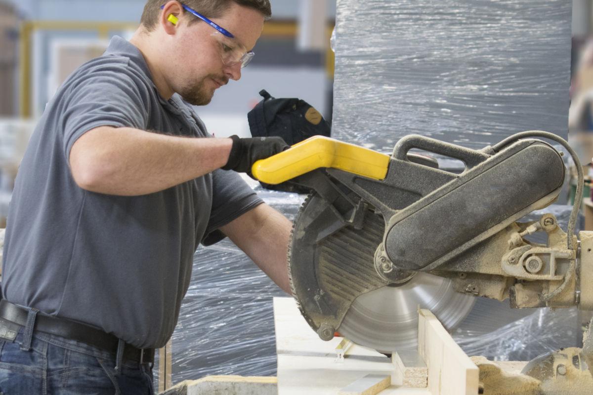 man cutting wood with circular saw in Aspen Factory